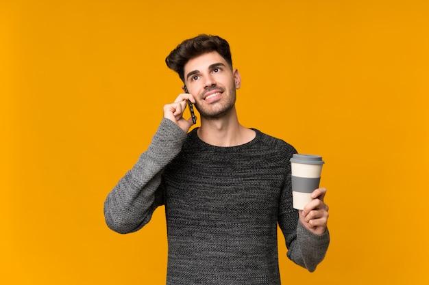 Junger mann über der lokalisierten wand, die kaffee hält, um und ein mobile wegzunehmen
