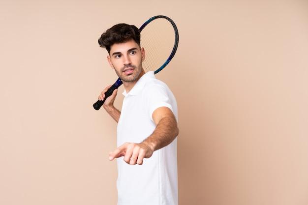 Junger mann über der lokalisierten wand, die tennis spielt