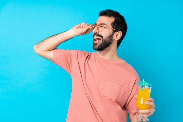 Junger mann über einen cocktail mit gläsern haltend und glücklich