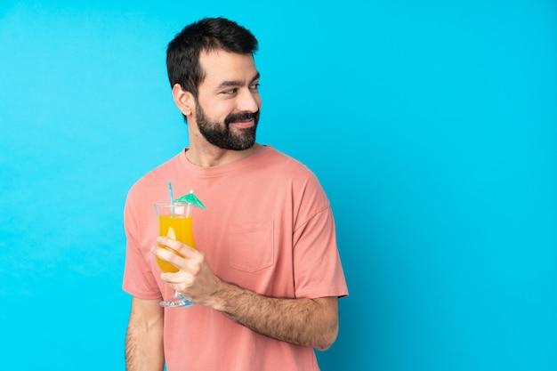 Junger mann über einen cocktail mit verschränkten armen und glücklich