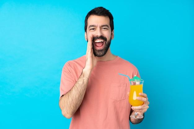 Junger mann über einen cocktail über blau schreiend mit offenem mund
