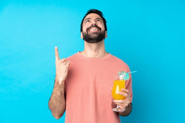 Junger mann über einen cocktail über isolierte blaue wand zeigend und überrascht
