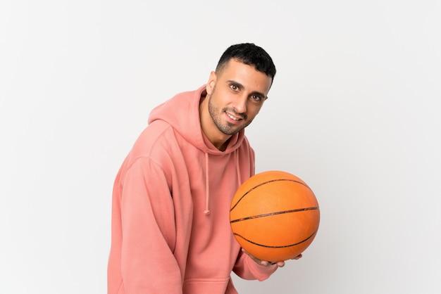 Junger mann über getrennter weißer wand mit kugel des basketballs