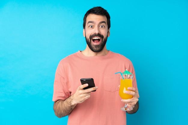 Junger mann über hält einen cocktail überrascht und sendet eine nachricht