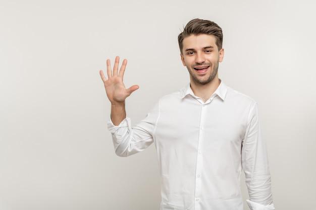 Junger mann über isoliertem weißem hintergrund, der fünf finger zeigt, während er isoliert über weiß lächelt