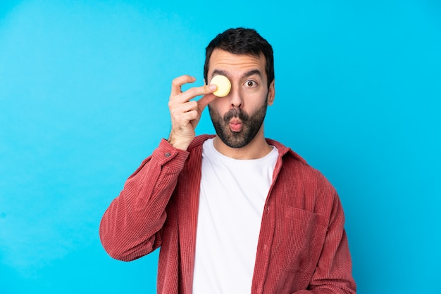 Junger mann über isolierter blauer wand, die bunte französische macarons mit lustigem gesicht hält