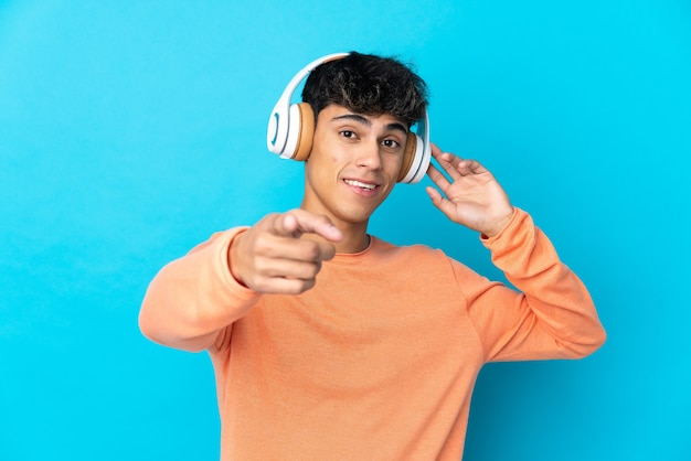 Junger mann über isolierter blauer wand, die musik hört und nach vorne zeigt