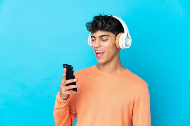 Junger mann über isolierter blauer wand, die musik mit einem handy hört und singt
