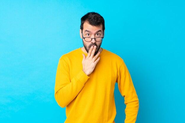 Junger mann über isolierter blauer wand mit brille und überrascht