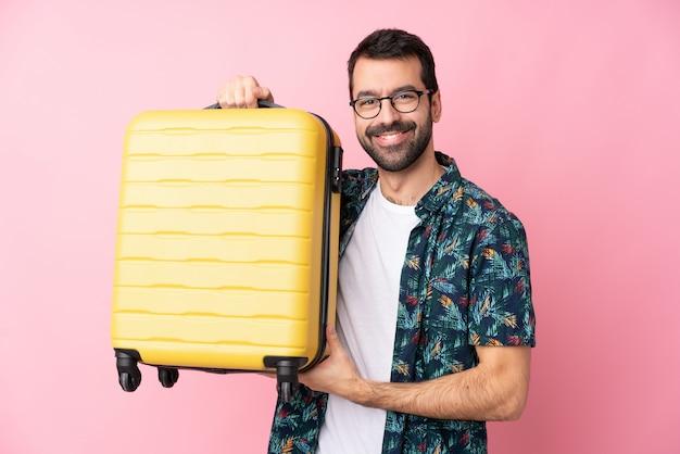 Junger mann über isolierter wand im urlaub mit reisekoffer