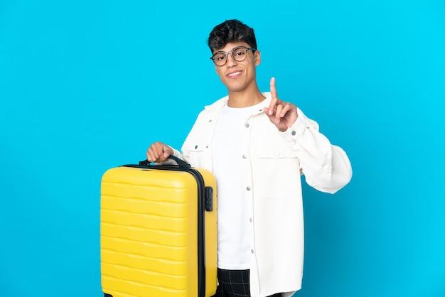 Junger mann über lokalisiertem blauem hintergrund im urlaub mit reisekoffer und zählen eines