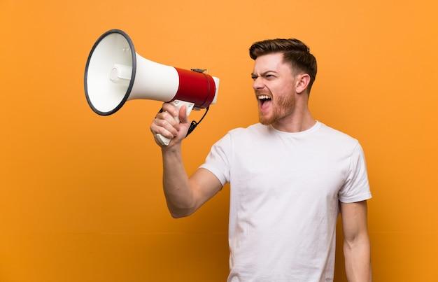 Junger mann über lokalisiertem hintergrund schreiend mit einem megaphon