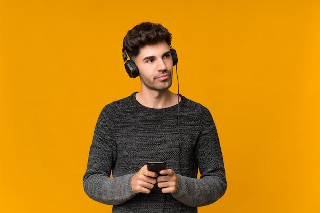 Junger mann über lokalisierter wand unter verwendung des mobiles mit kopfhörern und dem denken