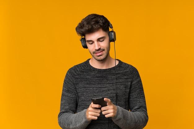 Junger mann über lokalisierter wand unter verwendung des mobiles mit kopfhörern