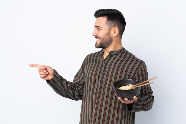 Junger mann über lokalisierter wand zeigend auf die seite, um ein produkt beim halten einer schüssel nudeln mit essstäbchen darzustellen