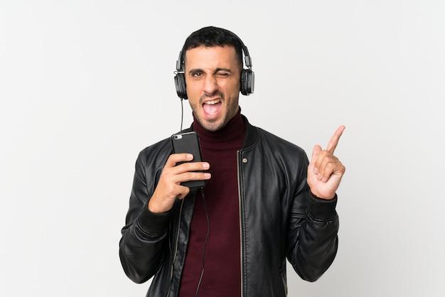 Junger mann über lokalisierter weißer wand unter verwendung des mobiles mit kopfhörern und dem gesang