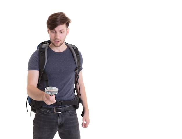 Junger mann überraschte das schauen des kompassses auf weißem hintergrund