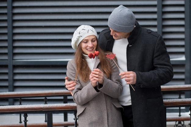 Junger mann überraschte seine freundin mit einem strauß herzen auf stock in der stadt. valentinstag. stehend und einander ansehend. hochwertiges foto
