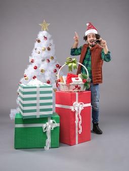 Junger mann um weihnachtsgeschenke auf grau Kostenlose Fotos