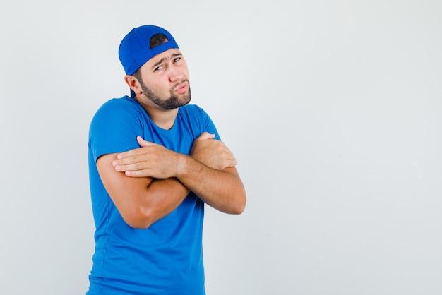 Junger mann umarmt sich oder fühlt sich kalt in blauem t-shirt und mütze und sieht bescheiden aus