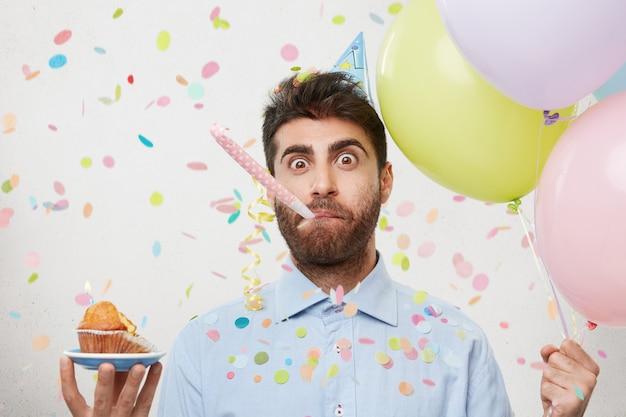 Junger mann, umgeben von konfetti mit cupcake und luftballons
