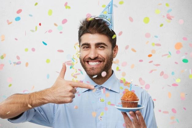 Junger mann, umgeben von konfetti mit cupcake