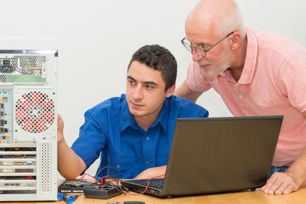 Junger mann und älterer festlegungscomputer