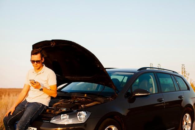 Junger mann und auto mit offener motorhaube
