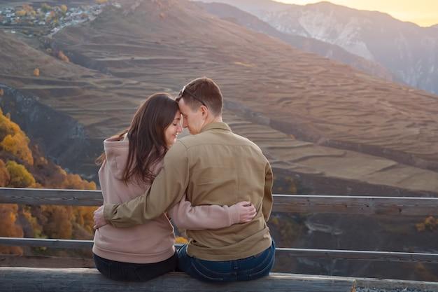 Junger mann und brünette freundin sitzt auf der bank am aussichtspunkt gegen malerische alte berge bei sonnenuntergang