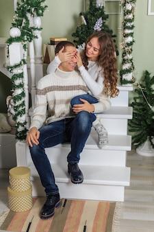 Junger mann und eine junge frau sitzen auf den stufen einer weißen treppe in einem haus