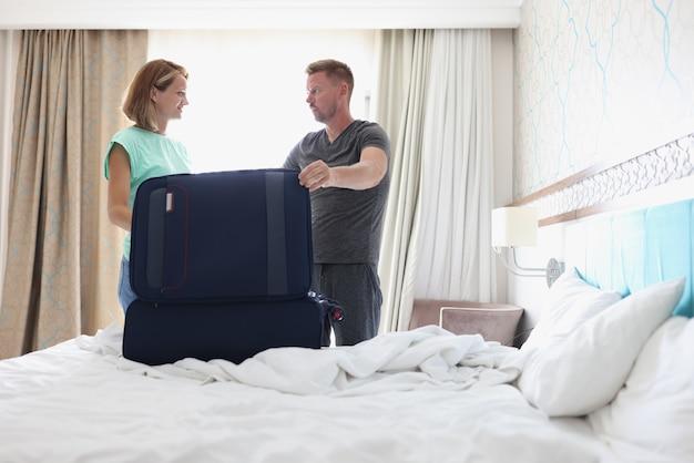 Junger mann und frau beim kofferpacken im schlafzimmer