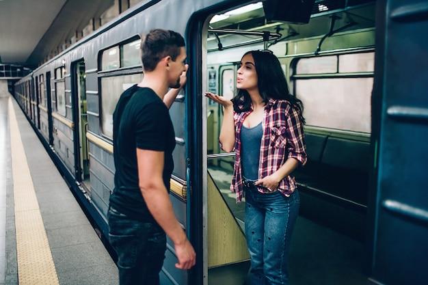 Junger mann und frau benutzen den untergrund. paar in der u-bahn. reizende junge frau senden dem mann küsse. guy schaut sie an und lächelt. gemeinsam alleine auf bahnsteig und u-bahn.