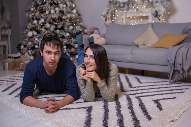 Junger mann und frau, die auf boden nahe sofa und weihnachtsbaum mit geschenken liegen und kamera betrachten.
