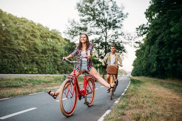 Junger mann und frau, die auf retro-fahrrädern gehen. glückliches paar auf vintage-fahrrädern. alte zyklen, romantische reise