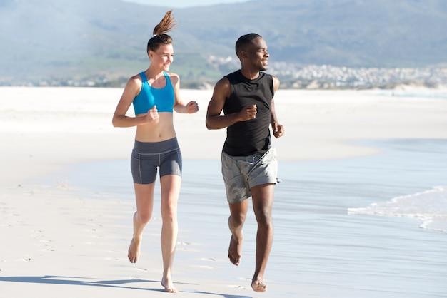 Junger mann und frau, die das laufen trainierend am strand tut