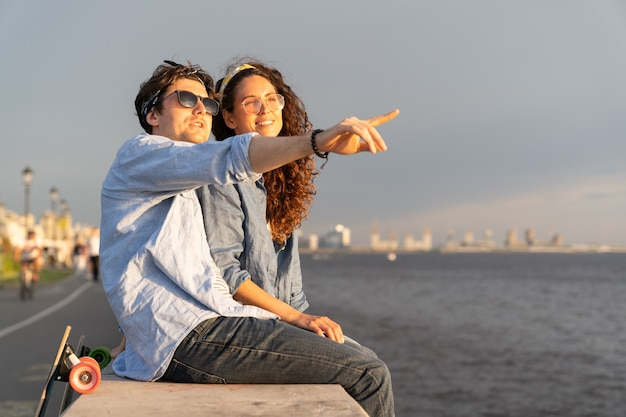 Junger mann und frau, die den sonnenuntergang am meer genießen, sitzen zusammen auf betonpflaster und schauen in den himmel
