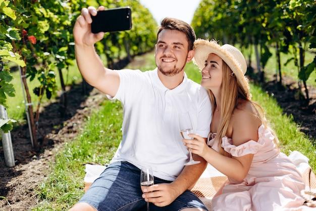 Junger mann und frau, die durch smartphone im weinberg selfy macht