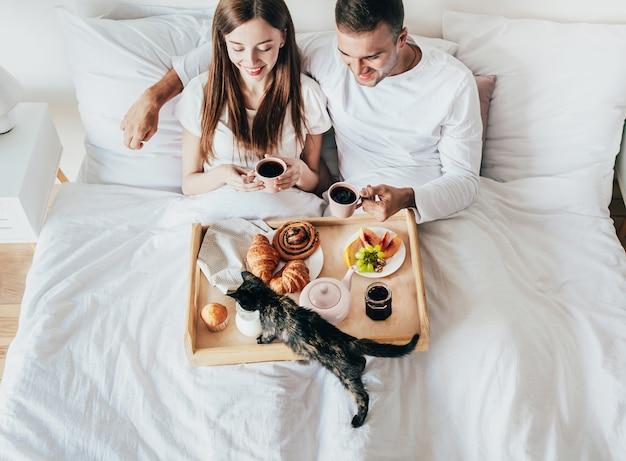 Junger mann und frau, die frühstück in einem weißen bett im schlafzimmer haben
