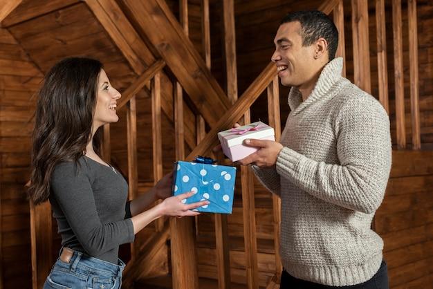 Junger mann und frau, die geschenke austauscht