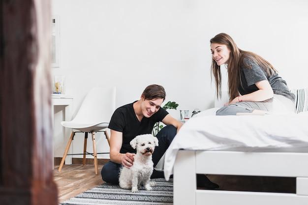 Junger mann und frau, die ihren hund im schlafzimmer betrachtet