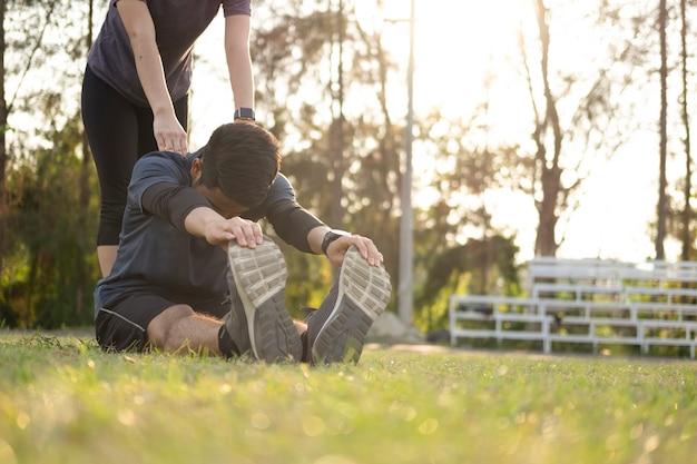 Junger mann und frau, die im park strecken.