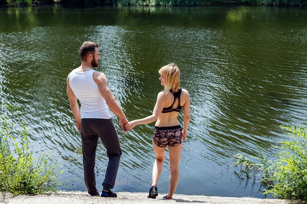 Junger mann und frau, die in den park nahe dem fluss geht.
