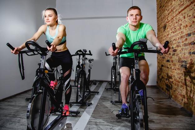Junger mann und frau, die in die turnhalle, die beine trainierend radfahrenfahrräder des herz trainings radfährt.