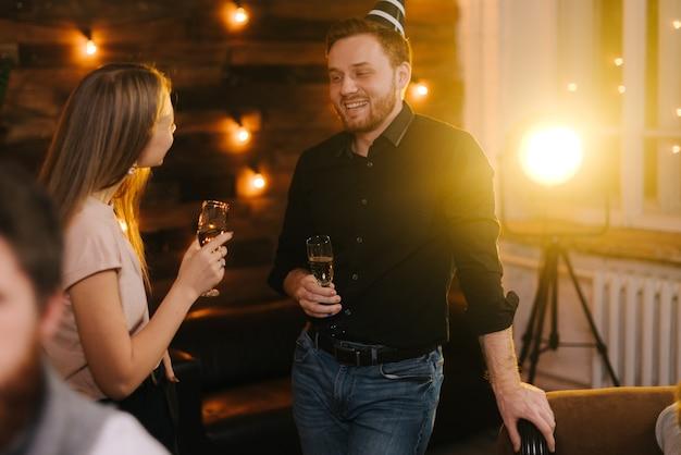 Junger mann und frau, die sich in einem festlich dekorierten haus unterhalten, das gläser champagner in der hand hält. junges paar spricht an silvester
