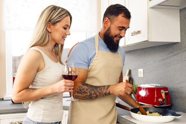 Junger mann und frau, die zusammen essen in der küche kochen, glückliches paar, das essen zubereitet?