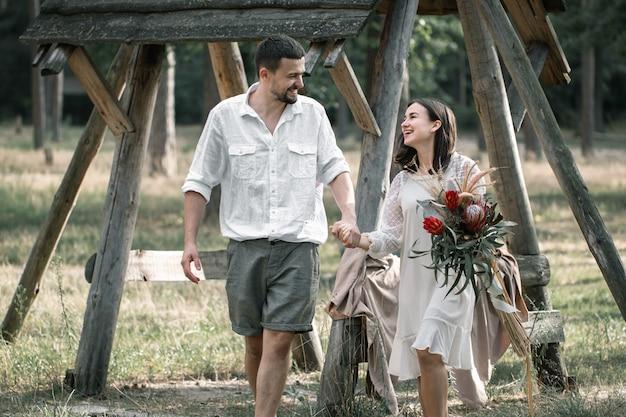 Junger mann und frau, elegant gekleidet, mit einem strauß exotischer blumen, spazieren im wald zu einem date in der natur.