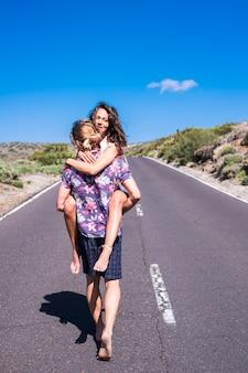 Junger mann und frau in beziehung gehen zusammen mitten auf einer langen straße am berg
