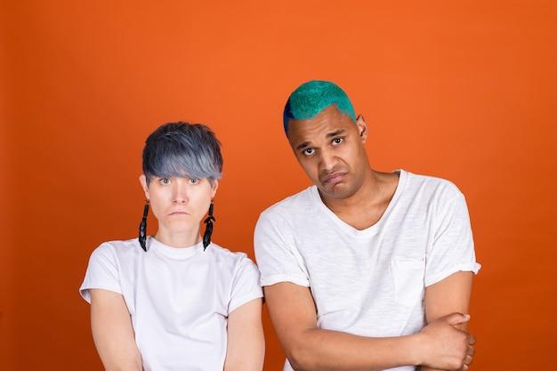 Junger mann und frau in lässigem weiß an orangefarbener wand sehen unglücklich aus mit der kamera
