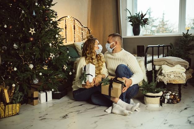 Junger mann und frau in masken, die einander schauen, während sie weihnachtsgeschenke in ihrem schlafzimmer halten
