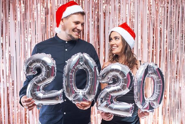 Junger mann und frau in roten sankt-hüten, die spaß mit 2020 metallischen ballonen haben.